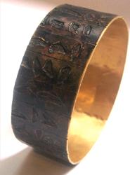 Un brazalete del autor, en bronce y chapado en oro.