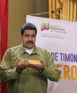 El presidente venezolano posa con un lingote de oro durante el anuncio de su Plan Oro.
